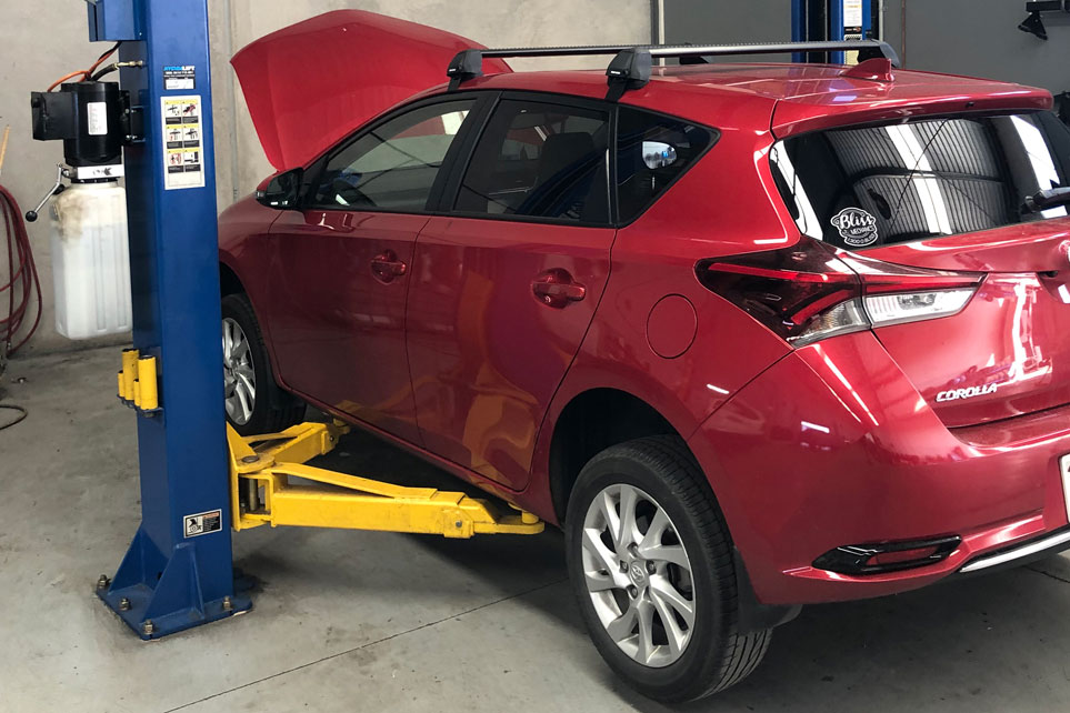 Red family car getting repaired